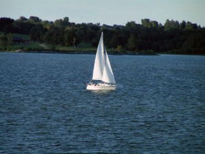 sail boat with waves around it heading toward land